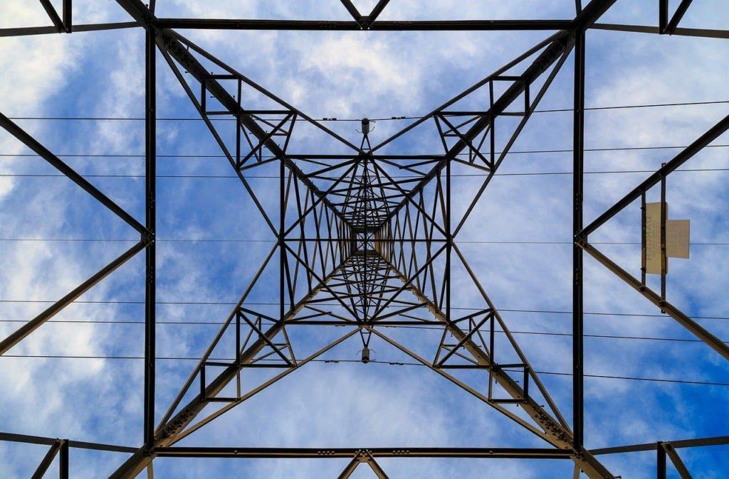 Electrical power transmission systems operators investigate transitioning to a Distributed Grid without compromising system strength. Image of electrical transmission line pylon.
